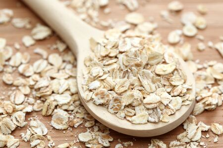 rolled oats: Rolled oats in the wooden spoon. Close-up.