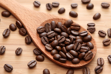 large bean: Coffee beans in a wooden spoon. Close-up.