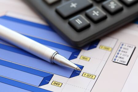 financial statements: Financial statements. Business Graph. ballpoint pen and calculator on a financial chart or Stock Market Data. Focus on ballpoint pen. Close-up. Stock Photo