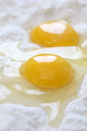 yolks: Two egg yolks and flour. Close-up. Stock Photo