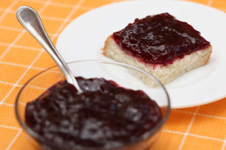 tea spoon: Slice of bread with cherry jam on a plate and glass bowl of jam with tea spoon. Focus on slice of bread. Close-up.