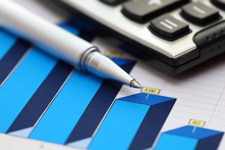 ballpoint pen: Financial statements. Business Graph. ballpoint pen and calculator on a financial chart or Stock Market Data. Focus on ballpoint pen. Close-up. Stock Photo