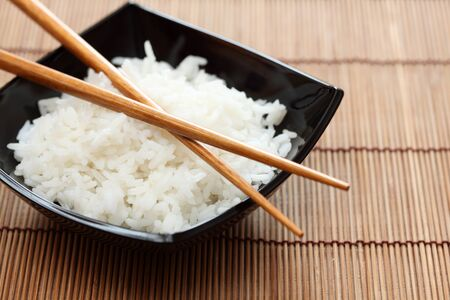 food staple: Bowl of rice and chopsticks on bamboo napkin. Close-up.
