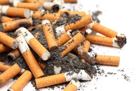 unhealthy living: Cigarette Butts on white background. Unhealthy habit. Close-up. Stock Photo
