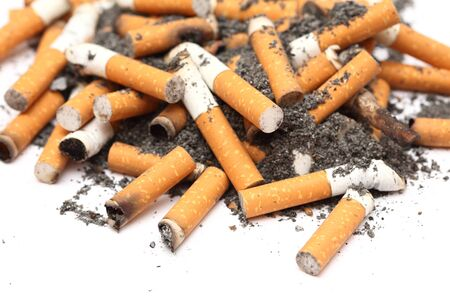 habit: Cigarette Butts heap on white background. Unhealthy habit. Close-up. Stock Photo