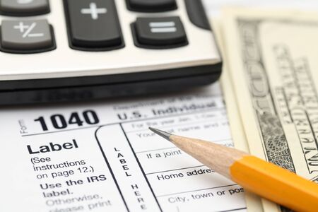 one hundred dollars: 1040 Tax Form with pencil, calculator and one hundred dollars