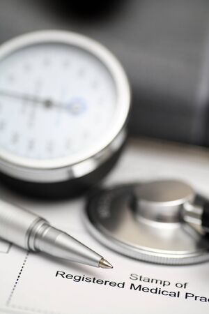 blood pressure gauge: Blood Pressure Gauge (shygmomanometer, stethoscope, cuff) and ballpoint pen on medical records. Focus on ballpoint pen. Shallow depth of field. Close-up. Stock Photo