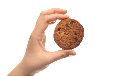 Oatmeal chocolate chip cookie in hand against white background. Close-up. Stock Photo