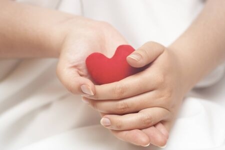 the merciful: Red heart in gentle woman%u2019s hands