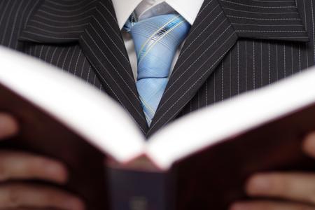 ビジネスマンを保持している、本を読んで