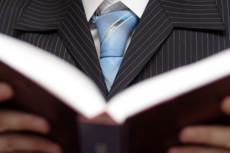 Businessman holding and reading book