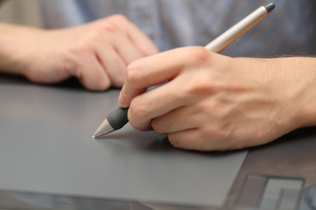 input device: Designer at work Using a pen on tablet. Close-up. Stock Photo