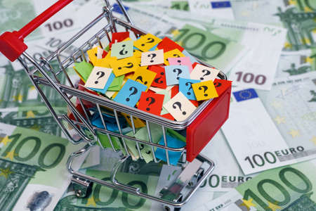 shopping questions: Shopping cart with question marks on one hundred euro banknotes.