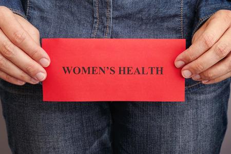 女性の健康の概念。彼女の手のフレーズの女性の健康と紙の赤い部分を保持している女性。