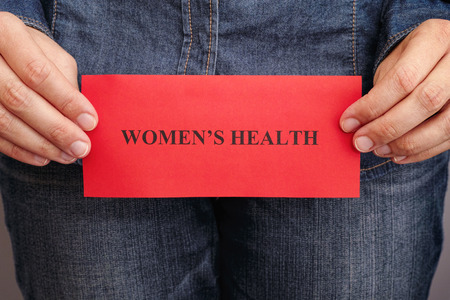 women's issues: Womens health concept. Woman holding red piece of paper with phrase Women's Health in her hands.