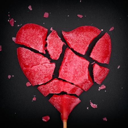 Broken red heart shaped lollipop. Closeup. Vignette. Standard-Bild
