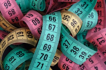 tailor measuring tape: Colorful measuring tapes pile. Close up.