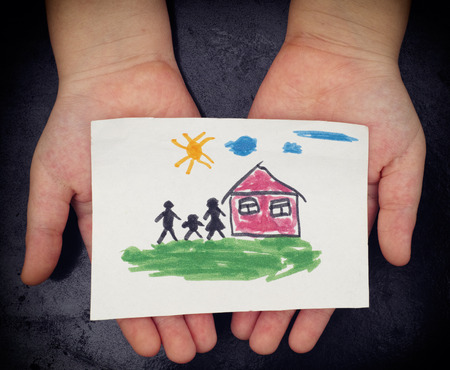 child drawing: Child holds a drawn house with family. Close up. Vignette.