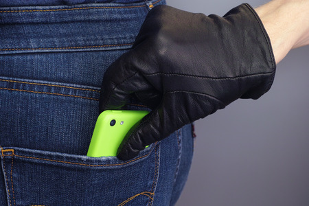 hands on pocket: Thief stealing mobile phone from back pocket of a woman. Stock Photo