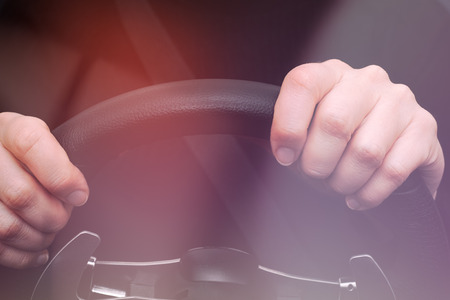 Womans hands on steering wheel of a car. Photo was taken through the windshield.