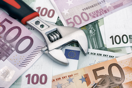 banconote euro: Chiave inglese regolabile su banconote in euro. Immagine concettuale. Archivio Fotografico