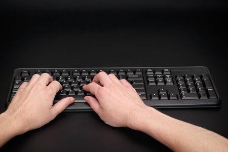 teclado de computadora: Escribiendo en el teclado del ordenador. Fondo negro. Foto de archivo