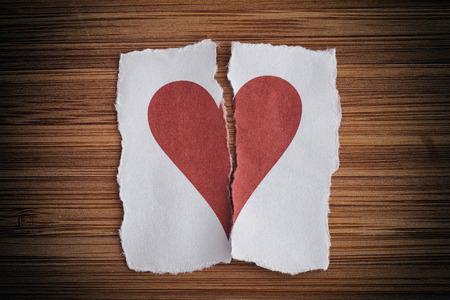 Broken paper heart on a wooden background. Light noise effect added. Vignette.