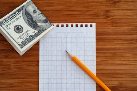 one sheet: Blank sheet of paper and pencil with one hundred dollars bill on a wooden background. Close up. Stock Photo