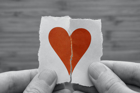 Man holds red broken paper heart in his hands. Black and white image with red paper heart. Vignette. Standard-Bild