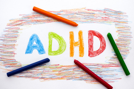 hyperactivity: ADHD written on sheet of paper by crayones. ADHD is Attention deficit hyperactivity disorder.