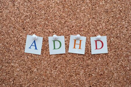 hyperactivity: ADHD letters pinned to a cork notice board. ADHD is Attention deficit hyperactivity disorder.