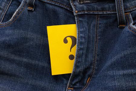 educacion sexual: Nota de papel amarilla con signo de interrogación aparece en pantalones vaqueros vuelan. Concepto de cuestiones sexuales.