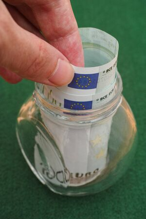 one hundred euro banknote: Man taking one hundred euro banknote out of jar. Close up.