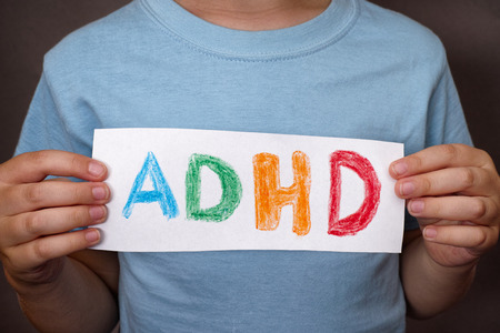 Young boy holds ADHD text written on sheet of paper. ADHD is Attention deficit hyperactivity disorder. Close up. Standard-Bild
