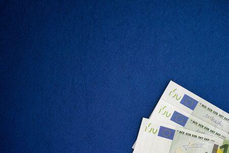 one hundred euro banknote: One hundred euro banknotes heap on a blue background. Vignette.