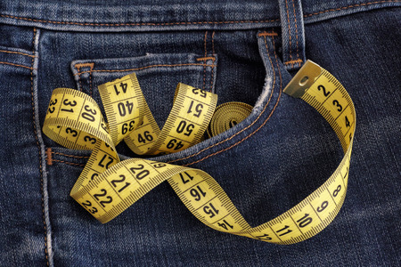 Jeans with tape measure in pocket. Diet concept.