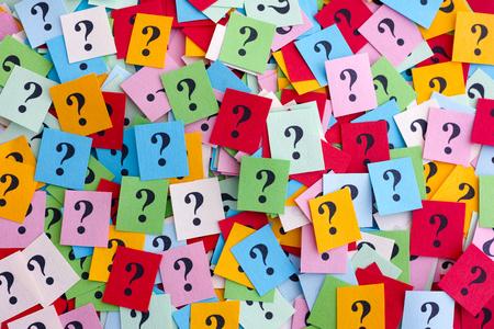 preguntando: Demasiadas preguntas. Pila de papel colorido observa con signos de interrogación. De cerca.