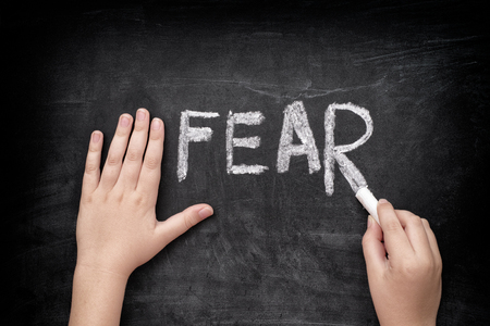 fear: Child writing word Fear on a blackboard. Stock Photo