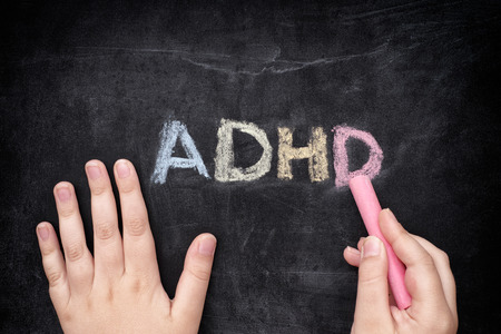 deficit: Child writing ADHD on blackboard. ADHD is Attention deficit hyperactivity disorder.