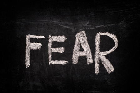 Word Fear on a blackboard writing with chalk. Close up.