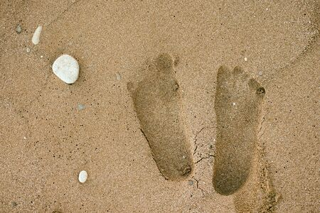 indentation: Human footprints on the sand. Close up.
