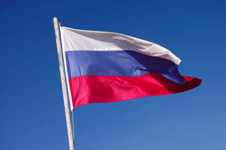 patriotism: Russian National Flag waving in the wind against blue sky.
