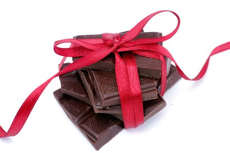 Dark chocolate with red ribbon on white background. Close up. Standard-Bild