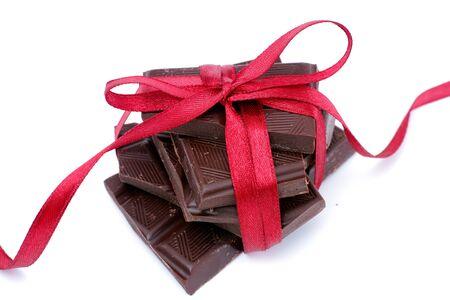 Dark chocolate with red ribbon on white background. Close up. Standard-Bild