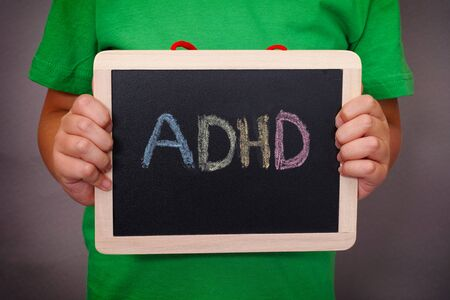 hyperactivity: Young boy holds ADHD text written on blackboard. ADHD is Attention deficit hyperactivity disorder. Close up. Stock Photo
