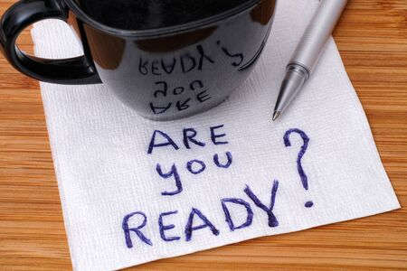 Are You Ready? handwriting on a napkin with cup of coffee. Close up. Stock Photo
