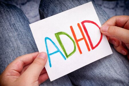 hyperactivity: Young boy holds ADHD text written on sheet of paper. ADHD is Attention deficit hyperactivity disorder. Close up. Stock Photo