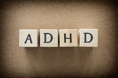 hyperactivity: ADHD abbreviation on wooden blocks. ADHD is Attention deficit hyperactivity disorder. Close up. Vignette.