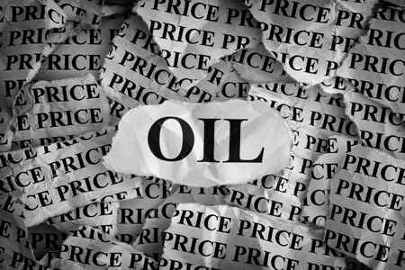 tearing down: Falling oil prices. Torn pieces of paper with the word Oil. Concept Image. Black and White. Closeup.