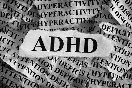 hyperactivity: Torn pieces of paper with abbreviation ADHD. Concept Image. Black and White. ADHD is Attention deficit hyperactivity disorder. Close up. Vignette.